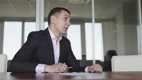 El hombre de negocios en traje y el lazo discuten un caso que se sienta en una tabla almacen de video