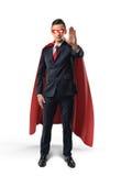 El hombre de negocios en un cabo rojo y la máscara de ojo roja con una mano aumentaron en la advertencia en el fondo blanco Imágenes de archivo libres de regalías