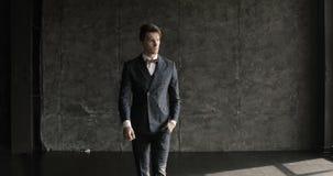 El hombre de negocios en un traje está caminando en un fondo gris almacen de metraje de vídeo