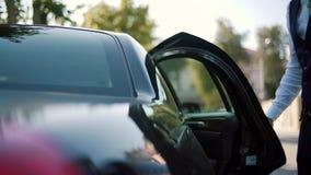 El hombre de negocios en un traje está caminando hacia un coche ejecutivo, cámara lenta almacen de metraje de vídeo