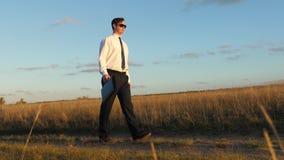 El hombre de negocios en vidrios con una cartera a disposición va en el camino Hombre libre y independiente Hombre de negocios en almacen de video