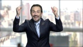 El hombre de negocios encantado aumentó sus manos en el entusiasmo almacen de video