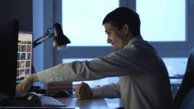 El hombre de negocios enojado en el funcionamiento del formalwear en el ordenador en oficina en la noche, después lanza los papel metrajes