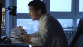 El hombre de negocios enojado en el funcionamiento del formalwear en el ordenador en oficina en la noche, despu?s lanza los papel metrajes