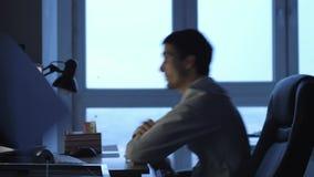 El hombre de negocios enojado en el funcionamiento del formalwear en el ordenador en oficina en la noche, despu?s lanza los papel almacen de metraje de vídeo