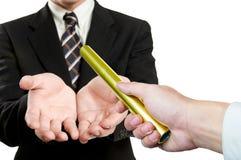 El hombre de negocios envía el boton de oro a otro encendido Imágenes de archivo libres de regalías