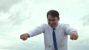 El hombre de negocios es super héroe en lazo en la prisa a ayudar El hombre de negocios feliz iba loco almacen de metraje de vídeo