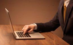 El hombre de negocios es traje que trabaja en el ordenador portátil Foto de archivo libre de regalías