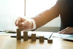 El hombre de negocios escoge monedas en la tabla, cuenta el dinero Negocio co fotos de archivo