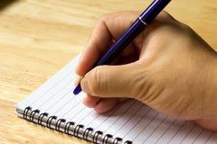 El hombre de negocios escribe con la pluma en el papel de nota fotos de archivo libres de regalías