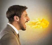 El hombre de negocios escupe el fuego Foto de archivo libre de regalías