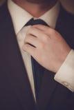 El hombre de negocios está atando la corbata Foto de archivo libre de regalías