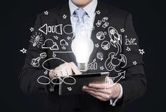 El hombre de negocios está buscando nuevas ideas del negocio en tableta Iconos del negocio del vuelo y una bombilla como concepto Fotografía de archivo
