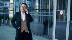 El hombre de negocios está caminando cerca de un edificio y está hablando en su teléfono Tiro épico rojo de la cámara del cine