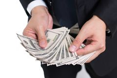 El hombre de negocios está contando billetes de banco de los dollas del hundread del dinero de la pila, después de trabajo, prima Fotografía de archivo