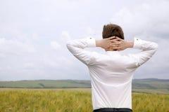 El hombre de negocios está descansando en el campo que piensa en alrededor el futuro Fotos de archivo