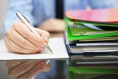 El hombre de negocios está escribiendo en el documento y mucha documentación es