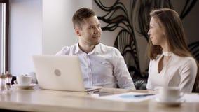 El hombre de negocios está esperando al colega Dos personas jovenes trabajan con un ordenador portátil en un café Están discutien metrajes
