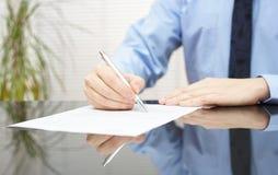 El hombre de negocios está firmando el contrato para concluir trato Fotografía de archivo
