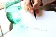 El hombre de negocios está firmando un contrato que se sienta en la oficina Fotos de archivo