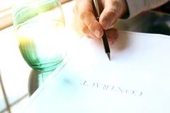 El hombre de negocios está firmando un contrato que se sienta en la oficina Foto de archivo libre de regalías
