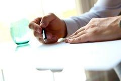 El hombre de negocios está firmando un contrato que se sienta en la oficina Foto de archivo