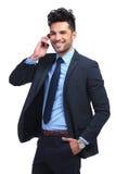 El hombre de negocios está hablando en su teléfono y sonríe Fotografía de archivo