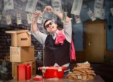 El hombre de negocios está lavando está planchando el dinero en el sótano foto de archivo