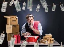 El hombre de negocios está lavando está planchando el dinero en espuma Fotografía de archivo libre de regalías