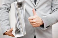 El hombre de negocios está llevando a cabo carpetas del documento y el mostrar manosea con los dedos encima de la GE Foto de archivo libre de regalías