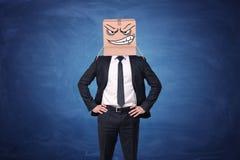 El hombre de negocios está llevando la caja de cartón con la cara enojada exhausta Imágenes de archivo libres de regalías