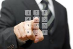 El hombre de negocios está marcando en telclado numérico virtual del teléfono Imagen de archivo libre de regalías