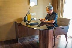 El hombre de negocios está mirando a la tableta fotografía de archivo libre de regalías