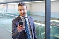 El hombre de negocios está mirando su teléfono móvil mientras que va al wor Imagen de archivo