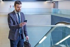El hombre de negocios está mirando su teléfono móvil mientras que va al wor Foto de archivo