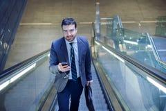 El hombre de negocios está mirando su teléfono móvil mientras que va al wor Fotografía de archivo