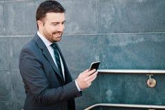 El hombre de negocios está mirando su teléfono móvil mientras que va al wor Fotos de archivo libres de regalías