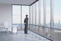 El hombre de negocios está mirando a través de la ventana de la esquina Fondo de Nueva York Foto de archivo libre de regalías