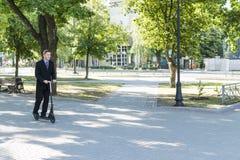 El hombre de negocios está montando en parque en la vespa Foto de archivo libre de regalías