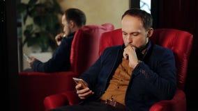 El hombre de negocios está trabajando en el café y el cigarrillo electrónico que fuma almacen de metraje de vídeo