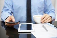 El hombre de negocios está utilizando el teléfono elegante y está leyendo el correo electrónico en la PC de la tableta Imágenes de archivo libres de regalías