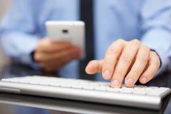El hombre de negocios está utilizando phablet mientras que mecanografía en el teclado del computet Foto de archivo libre de regalías