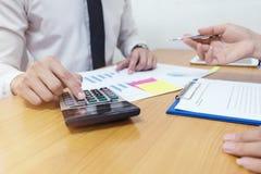 El hombre de negocios está utilizando una calculadora para calcular los números con fotos de archivo libres de regalías