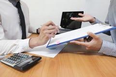 El hombre de negocios está utilizando una pluma para los datos financieros que analiza la cuenta imagen de archivo