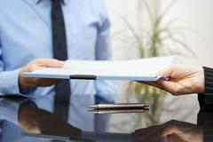 El hombre de negocios está pasando el acuerdo firmado al cliente después de successf Fotos de archivo