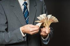 El hombre de negocios está sosteniendo el efectivo, fan de cincuenta euros La persona cuenta el dinero Manos del hombre de negoci Fotos de archivo libres de regalías