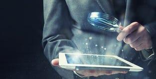 El hombre de negocios examina una tableta con una lupa Concepto de seguridad de Internet fotos de archivo libres de regalías