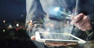 El hombre de negocios examina una tableta con una lupa Concepto de seguridad de Internet foto de archivo