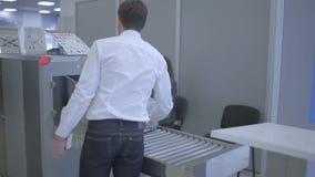 El hombre de negocios explora su equipaje con la máquina de radiografía en el aeropuerto almacen de metraje de vídeo