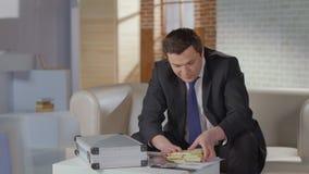 El hombre de negocios extático ase el dinero de la cartera, éxito, avaricia almacen de video